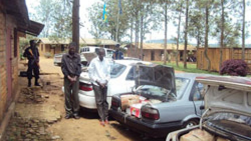 The two suspects arrested for trafficking illicit alcohol stand next to their impounded vehicles at Nyagatare Police post (Photo Dan Ngabonziza).