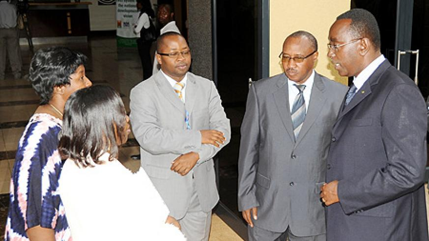 Prime Minister Bernard Makuza (R) speaks to the Permanent Secretary at the Ministry of Health Dr. Binagwaho after opening the international conference on cervical cancer. Looking on are Ministers Musoni and Nsanzabaganwa (L) and Dr. Fidel Ngabo (Photo J M