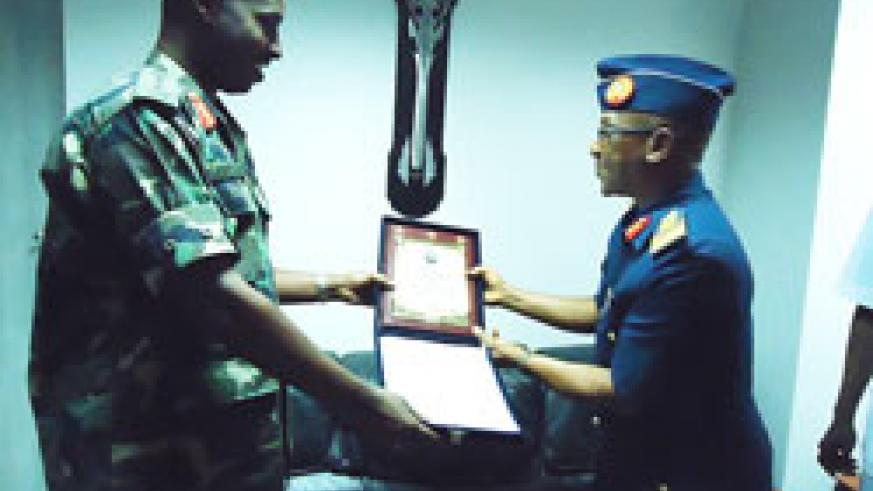 CDS Lt Gn Charles Kayonga receives a gift from Nigerian Air Vice Marshal Ahmed Tijjani Mu'azu, yesterday (Courtsey Photo)
