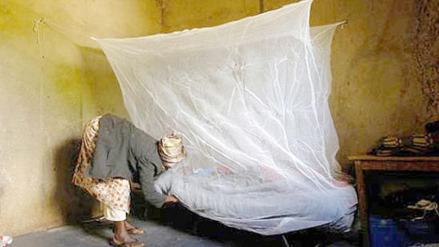 A Woman in Rwanda installs moquito netting over her son's bed in an effort to prevent the spread of malaria.