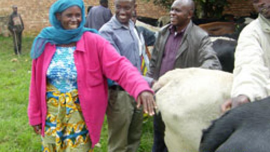 One of the beneficiaries receives her cow from local leaders. (Courtesy photo)