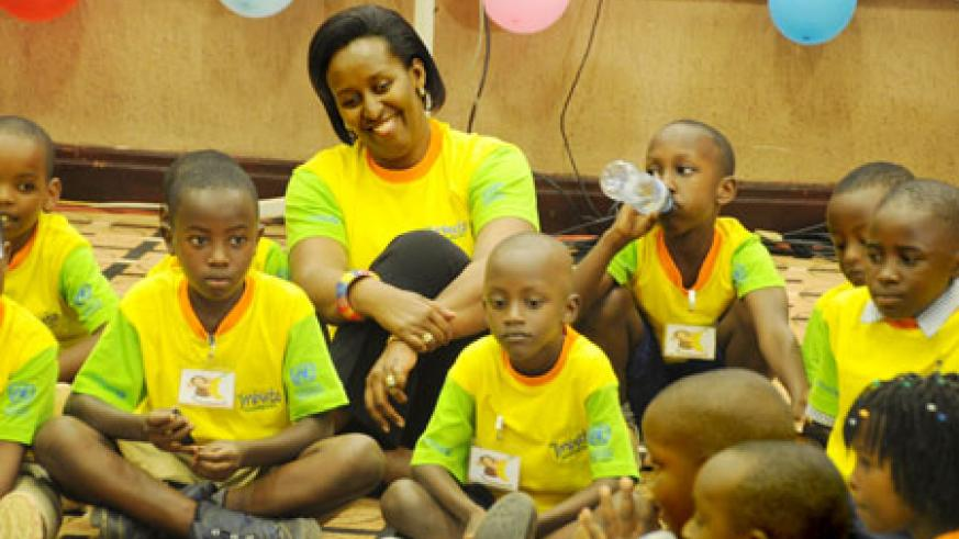 First Lady  Jeannette Kagame shares a light moment with children at Serena Hotel during a function to mark the Reading Day (Photo T.Kisambira).