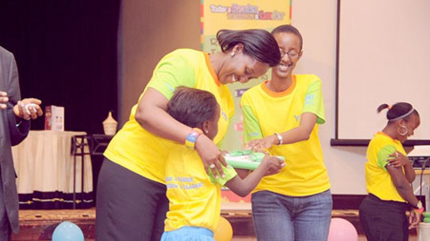 The First Lady handing over an XO laptop to one of the best performers during the competition.