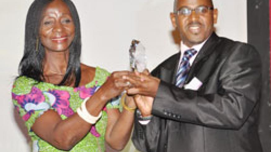Grace Mutsinzi (Right) the Division Manager ICT Planning and Coordination receives the e-Soko award (Courtesy photo)