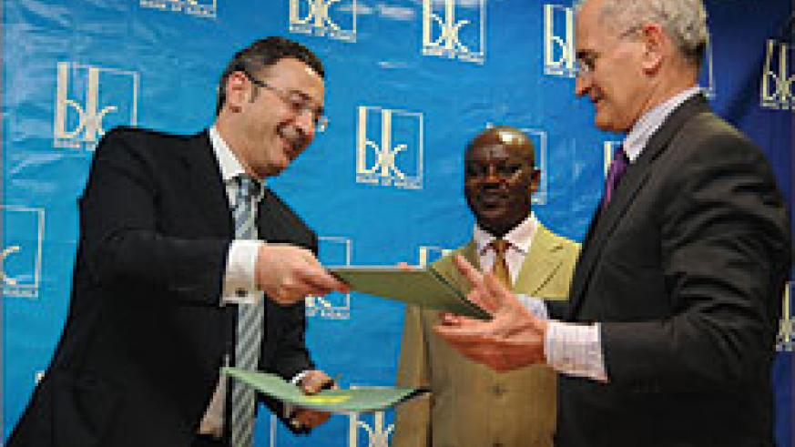 BK's Chairman Board of Directors, Lado Gurgenidze exchange documents with Yves Terracol, the Regional Director of AFD after the signing. Looking on is BK's COO, Lawson Naibo  (Photo T.Kisambira)