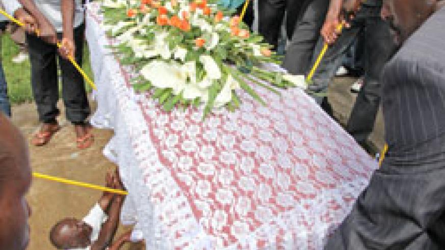Relatives lower one of the 38 caskets of the victims laid to rest yesterday (Photo T.kisambira