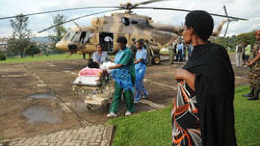 A relative of one of the Tanzanian road accident victim watches as the RDF air rescue team transfer patients to King Faisal Hospital, yesterday. (Photo J Mbanda)