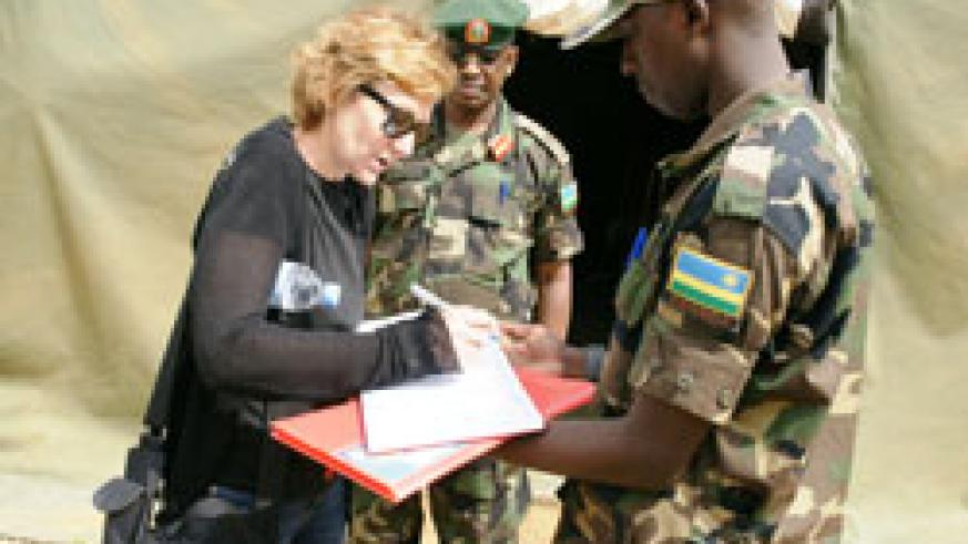 Monica Stein-Olson, professor of strategic planning at the US war college signs the visitors book at the Rwanda Military Academy-Gako