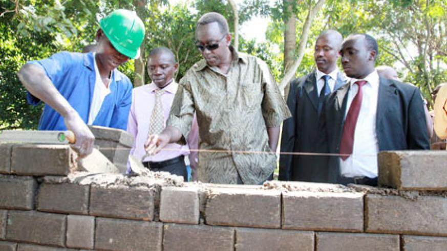 A student demonstrates Prime Minister Bernard Makuza how to build
