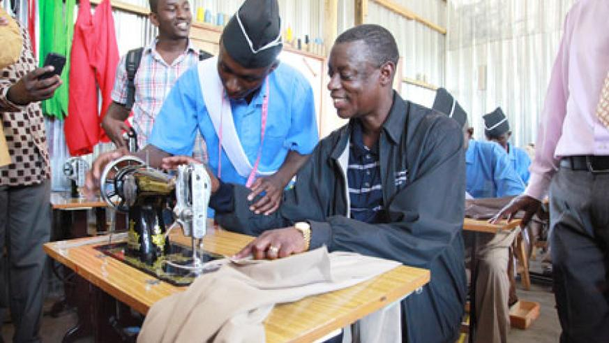A student shows James Kabarebe the minister of Defense how a sewing machine works
