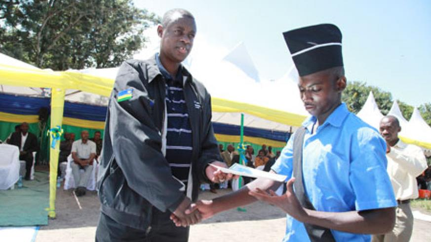 James Kabarebe the minister of defense presents an award to Abdulilah Nkundimana the best student in Commercial farming