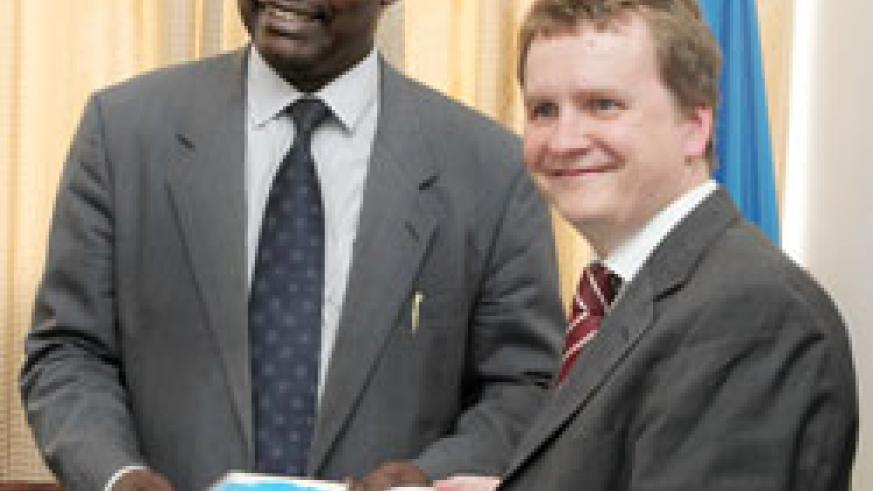 Nils Warmer hands over the Atlas to the Minister of Commerce, Francois Kanimba (Photo; T. Kisambira)