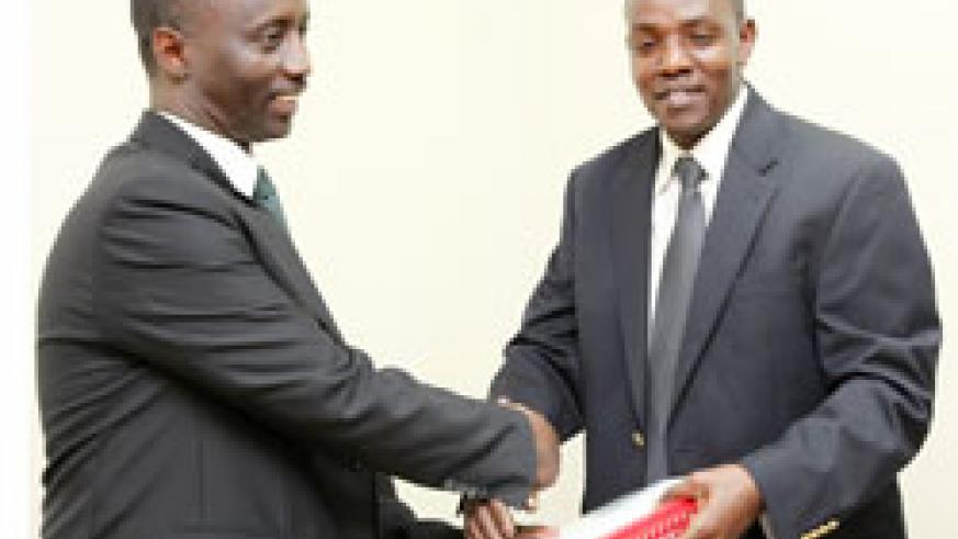 The new National Agriculture and Export board boss Alex Kanyankole (L) receives documents from the former director of RHODA Dr. Ndambe Nzaramba (Photo; T. Kisambira)