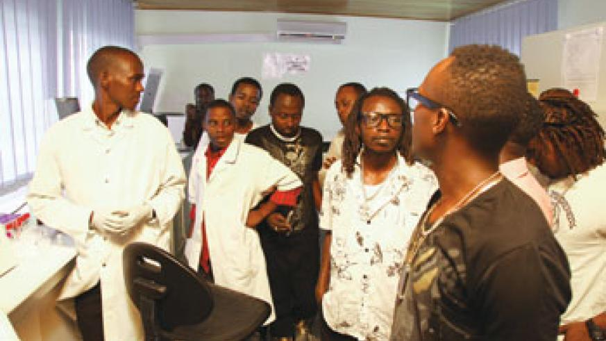 A specialist (in a white laboratory gown) briefs the artists.