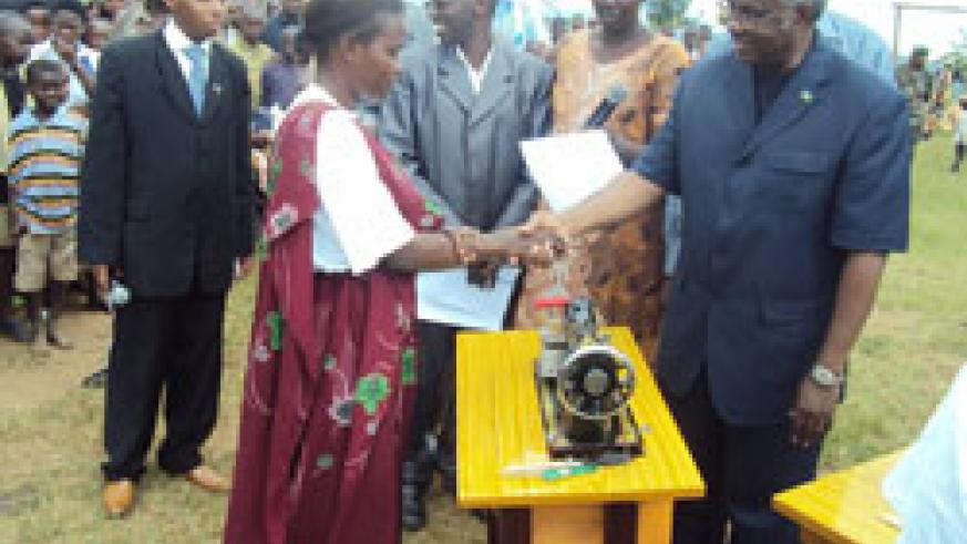 The Minister of Disaster Management and Refugee Affairs Gen. Marcel Gatsinzi hands over a sewing machine to one of the beneficiaries (Photo; JP. Bucyensenge)