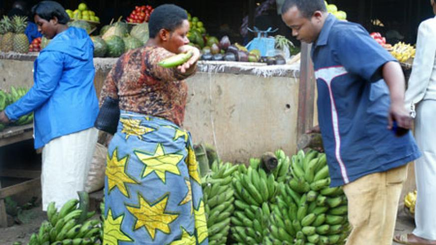 A buyer checks out a bunch of Bananas at Kimironko Market, yesterday. Food prices are expected to ease in June (Photo T.Kisambira)