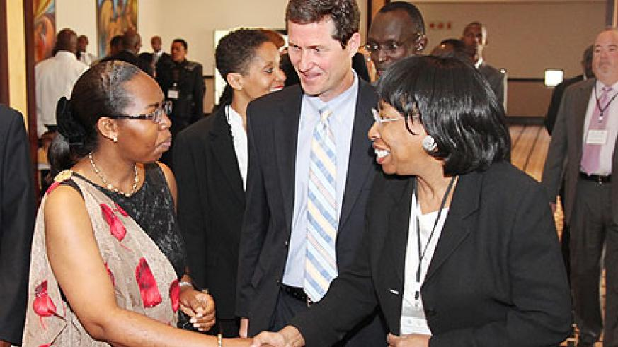 One of the participants, Bernice Donald (L) , talks to Chief Justice Cyanzayire as Stephen Gardner from the Commercial Law Development Programme (USA) looks on. (Photo T.Kisambira)