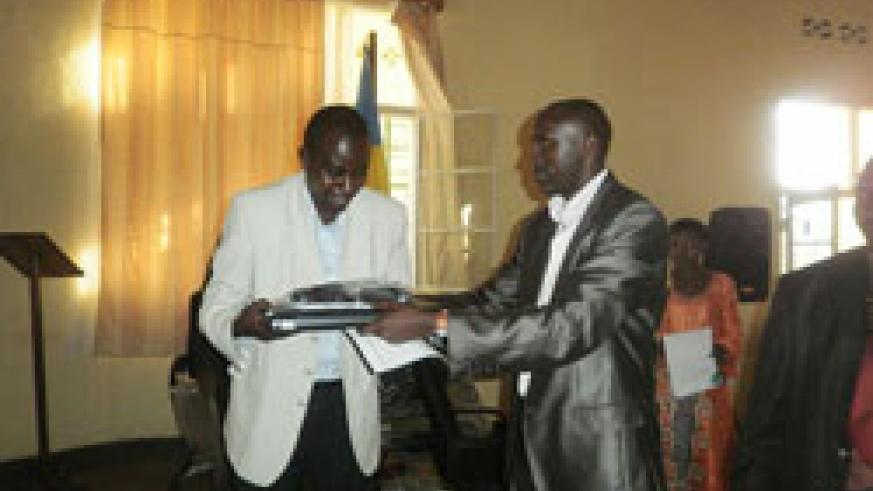 Nyamasheke Mayor, Jean Baptiste Habyarimana, hands over a laptop to Bushenge Sector Executive Secretary (Courtesy photo)