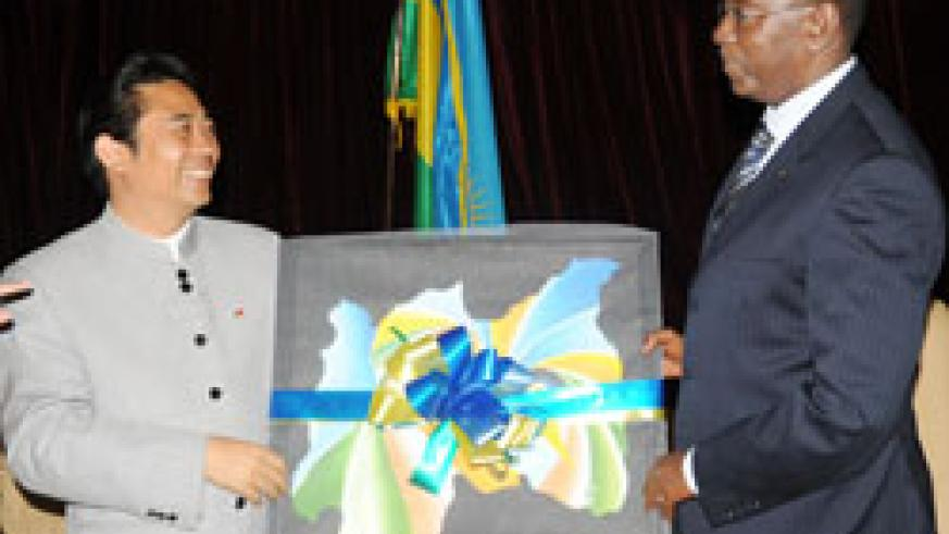 Prime Minister Bernard Makuza (R) presents a gift to the head of the Chinese delegation, Junqing Lu. (Photo J Mbanda)