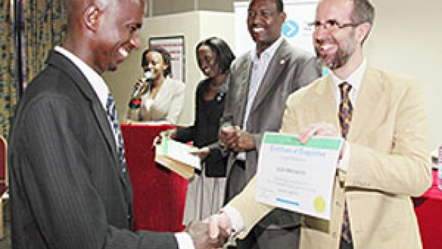 Alex Mwesigwa gets a certificate from Tonny Vetter DOT's senior director, operations as Protais Mitali the Minister of Youth Culture and Sports looks on (Photo T.Kisambira)
