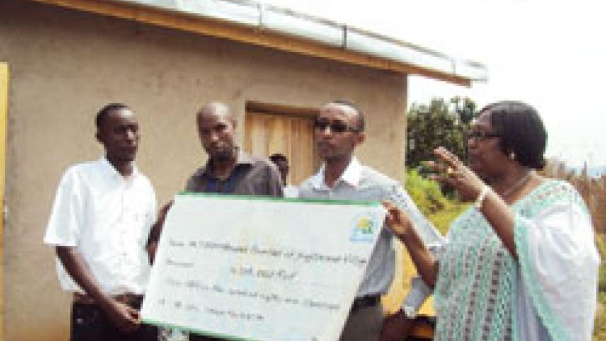 François Régis Gatarayiha (with glasses), the acting Director General of RURA, hands over a cheque of over to Kagitarama Survivor's Association (Photo D Sabiiti.)