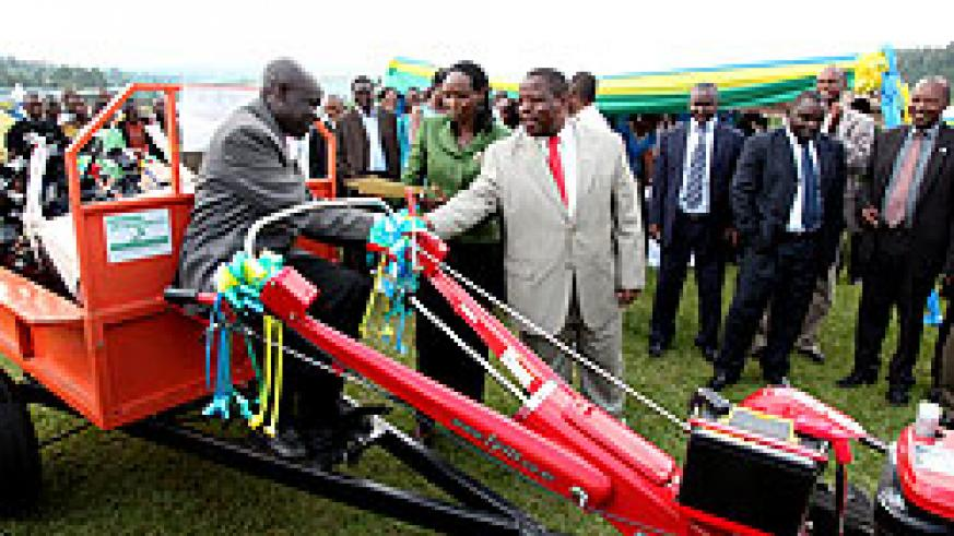 The Governor of the Northern Province, Aime Bosenibamwe (R), congratulates Telesphore Rucibiraro (seated on tractor) who emerged the best farmer during this year's agricultural expo yesterday, as the Agriculture Minister Dr. Agnes Kalibata hands to him a