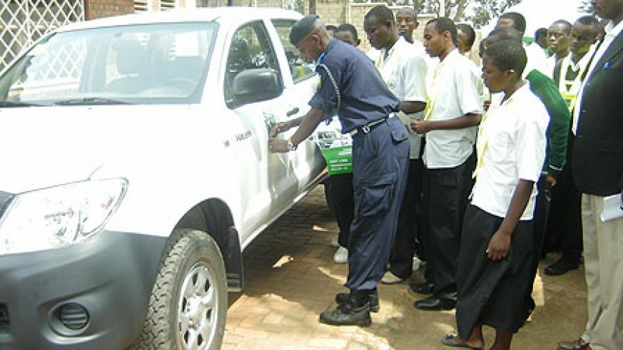 The Karongi District Police Commander demonstrates to the students how to place the stickers during the Road Safety Week (photo S Nkurunziza