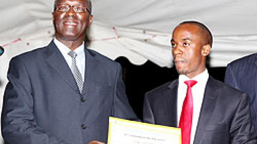 Minister of labour Hon. Anastase Murekezi (L) awards a certificate to Edmond Tubanambazi who was nominated as the best employee in the ministry yesterday