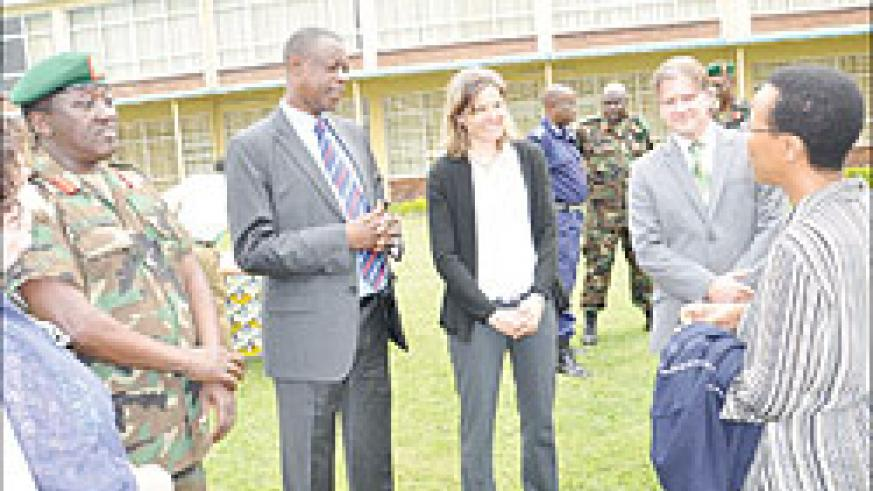 Rose Mukankomeje (R) chats with Gen. James Kabarebe (Third Left) as facilitators look on during the closing of the Environmental Security workshop in Musanze