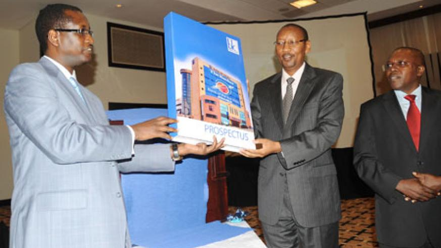 L-R;Bank of Kigali MD, James Gatera, Finance Minister, John Rwangombwa, and the Head of Capital Markets Advisory Council, Robert Mathu, unveil the BK Prospectus. (Photo/J Mbanda)