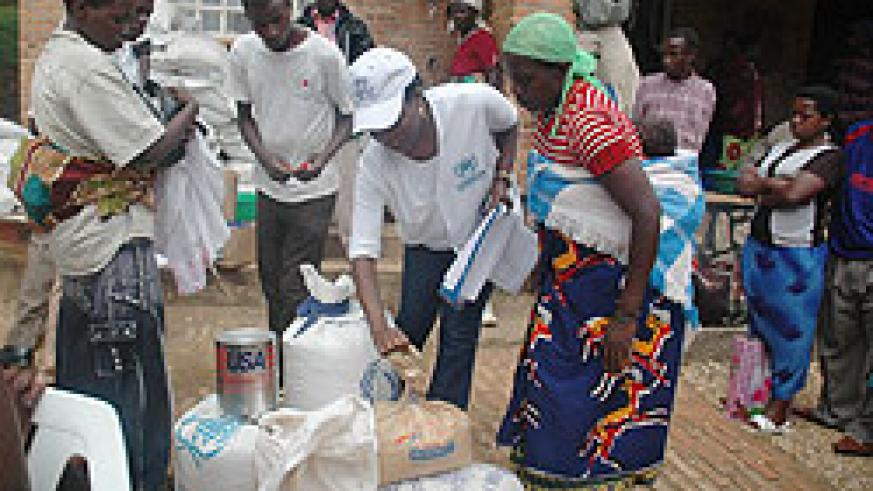 Returnees from Uganda receive food items at a transit camp  before heading to their respective homes. More have returned from DRC (File photo)