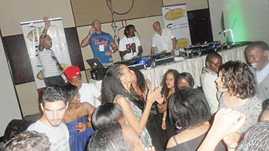 DJ Kaytrixx (2nd right in the extreme  background) spins the wheels of steel .