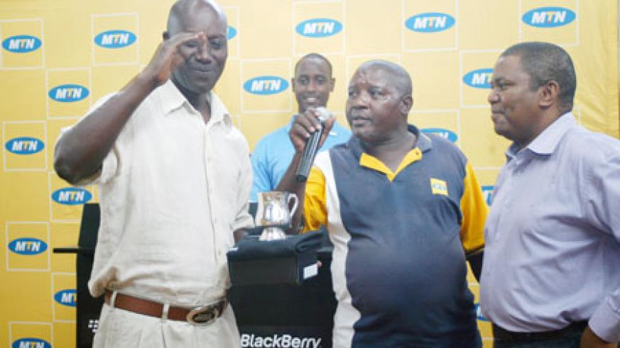 WINNER'S SMILE; Joseph Semwaga  (Left) receives a trophy after winning a past tournament. The golfer reigned supreme in yesterday's Liberation Day tournament. (File Photo)