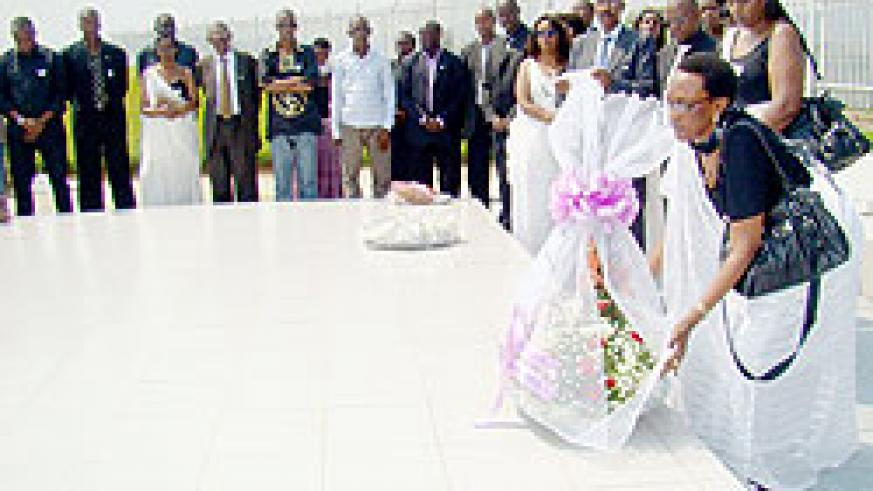 Marie Immaculee Ingabire lays a wreath at the mass grave. (Photo. G. Mugoya)