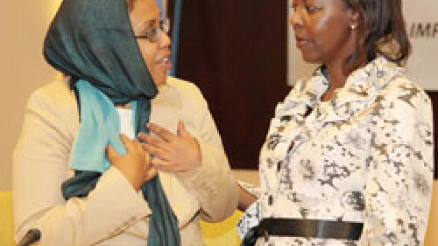 Hon Zahra Samantar( L) the Somalian Minister for Women Affairs and Human Rights chats with Louise Mushikiwabo of Foreign Affairs at the meeting, yesterday. (Photo T.Kisambira)