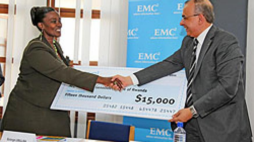 Mohammed Amin (R) the Regional Manager of the Turkish firm hands over the cheque to Solange Umulisa of AEGIS Trust on Tuesday (Photo T.Kisambira)