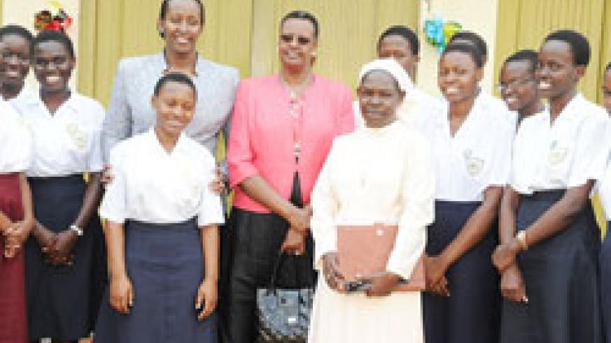 First Ladies, Mrs. Kagame (L) and Mrs. Museveni with Sister Seraphine, the headmistress of Namagunga girls and students from the school, yesterday.(Courtesy photo)