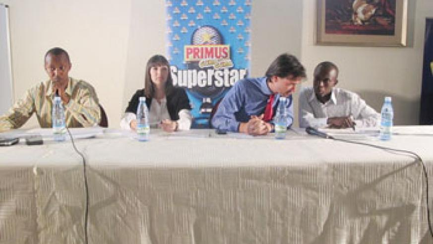 (R-L) An official from Bralirwa chats with Alexander Koch, Bralirwa's Commercial Director during a press conference at Top Tower Hotel. Looking on (from left) is Joseph Mushyoma, the CEO of East African Promoters (Photo / Linda)