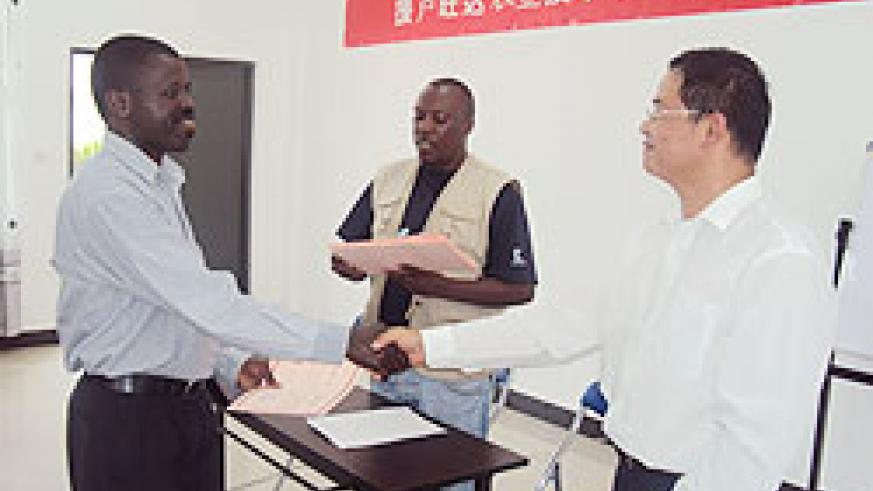 Lin Yingxing the centre manager where the training was conducted (R) hands a certificate to one of the  participants  (Photo JP Bucyensenge)
