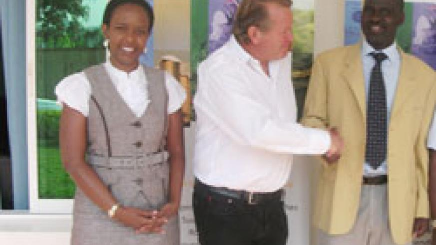 NFC Boss Julian Ozanne (c) with  the Minister Kamanzi of Natural Resources as RDB's Clare Akamanzi looks on after signing the agreement, yesterday. (Courtesy Photo)