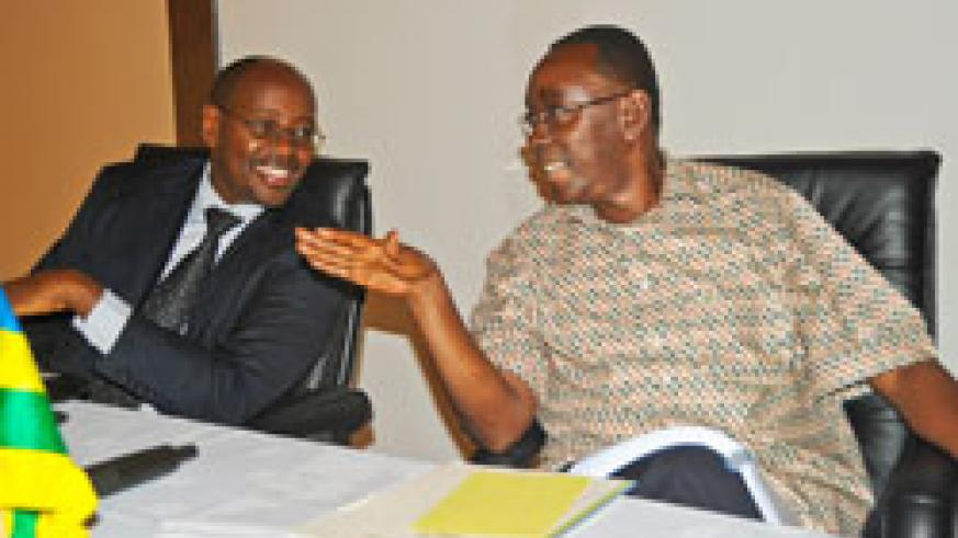 Prime Minister Bernard Makuza (R) chats with Local Government Minister James Musoni during the Local Government authorities' performance contracts review yesterday. (Photo J Mbanda)