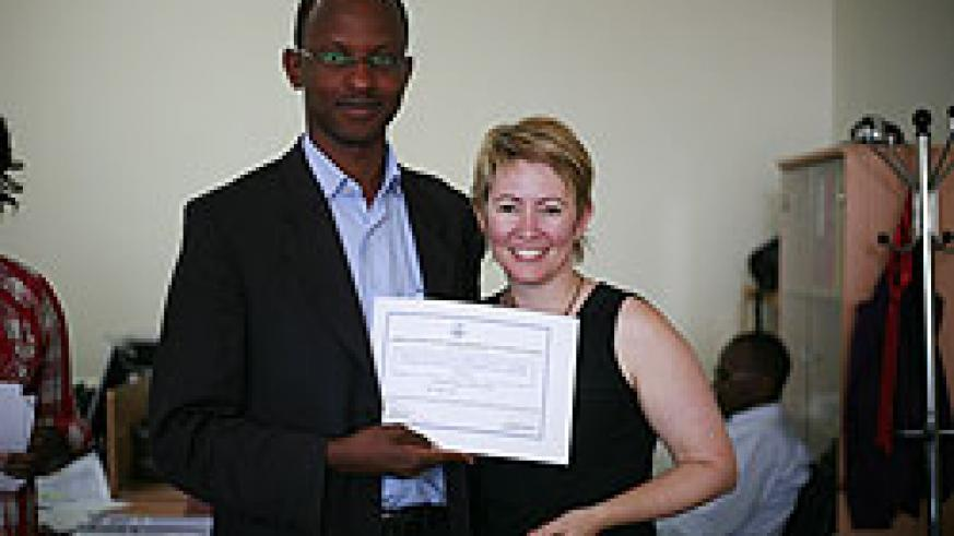 A trainee (L) receives a cerfiticate of participation from Kellie Krake of International Bridges to Justice (Courtesy Photo)