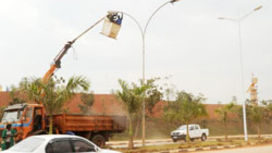 Kigali City Council employees mount streetlights in Kigali City. Kibungo authorities will spend a Rwf350 million to light up the town. (File photo)