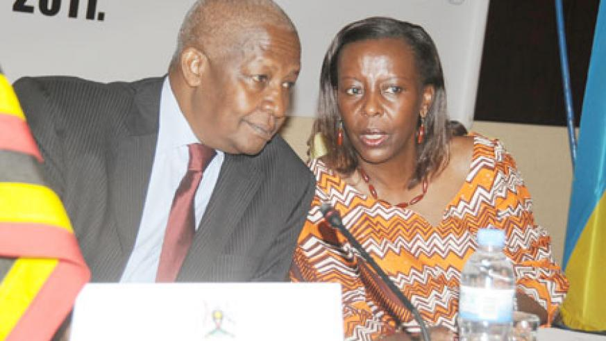 Foreign Ministers, Sam Kutesa of Uganda (L) and Louise Mushikiwabo of Rwanda consult during the 9th JPC yesterday. The New Times/ John Mbanda.