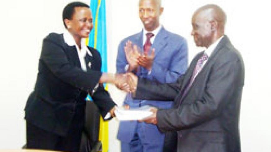 Mary Gahonzire (L) hands over to Paul Rwarakabije as Minister Fazil Harelimana looks on. The New Times Courtsey Photo.