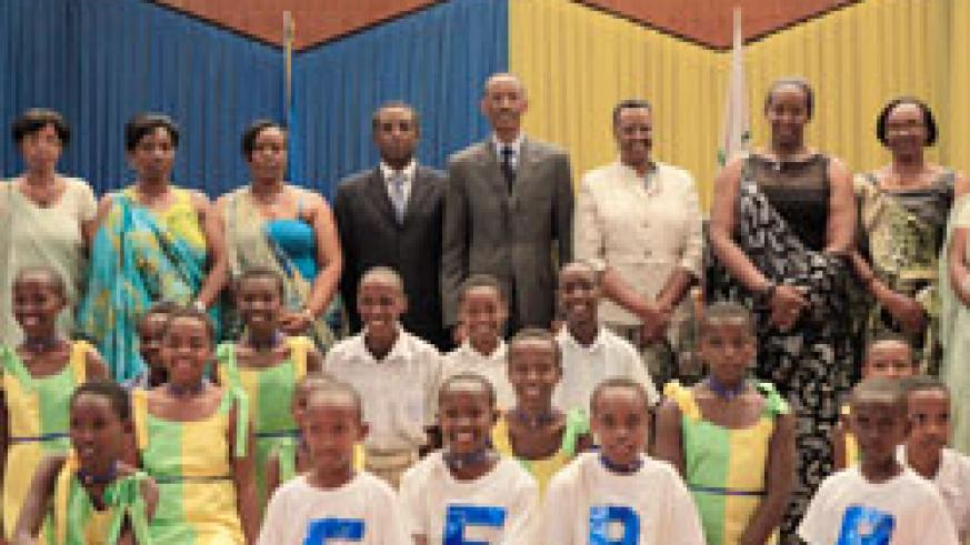 President Kagame and the First Ladies of Rwanda and Uganda, in a group photo with the House leaders, members of the Rwanda Women Parliament Forum and young children during the event to celebrate 15th anniversary of the Forum in Parliament, yesterday. Th