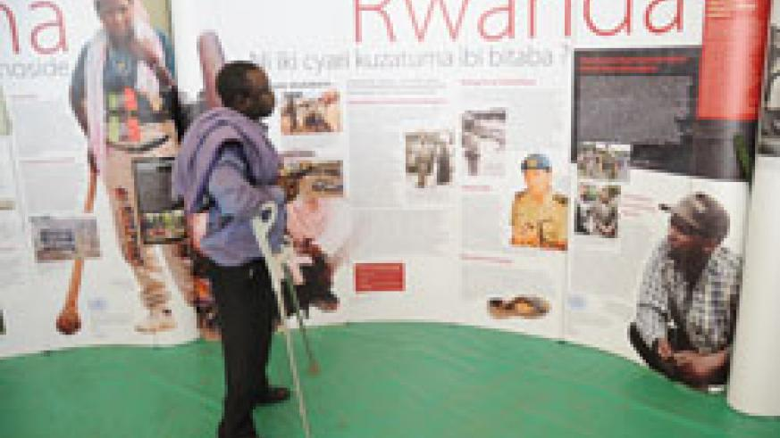 A man keenly examines pictures that reflect the 1994 Genocide  against Tutsi recently.Ibuka has called for more value to Genocide crimes. The New Times File.