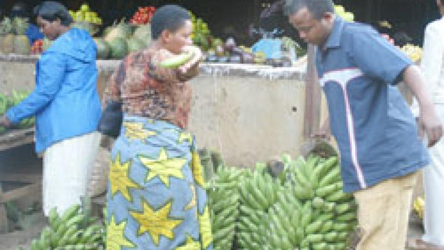 A man buys Bananas from Kimironko market. EAC boss has called for the implementation of strategies designed to ensure food security in the region. The New Times / File.