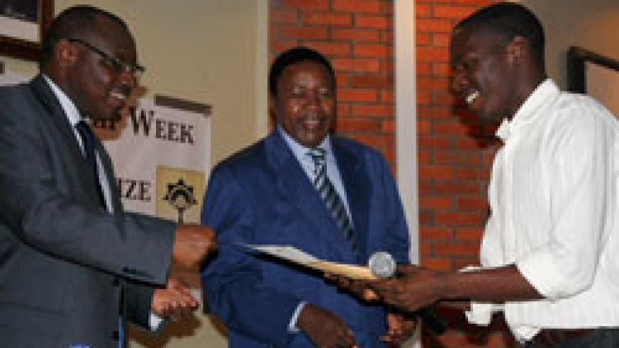 BNR GovernorGatete (Right) hands the African Innovative Prize to the winner Patrice Habinshuti, as KIST Vice Rector Prof John Mshana looks on. The New Times /Emma Munyaneza.