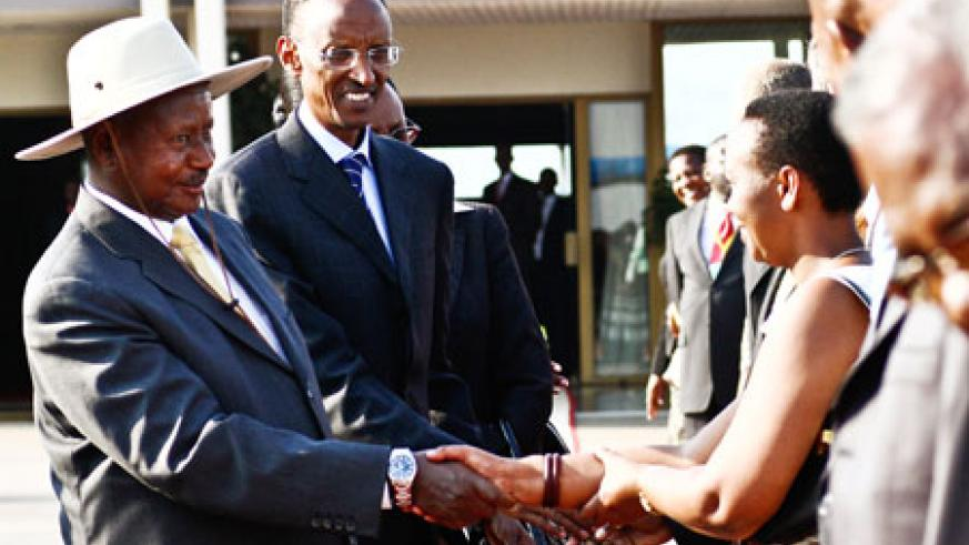 Presidents Museveni (L) and Kagame greet officials at Kigali International Airport yesterday shortly before the former's departure after a four-day state visit to Rwanda. The New Times / James Akena